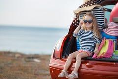 De gelukkige zitting van het babymeisje in de autoboomstam Stock Foto