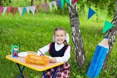 De gelukkige zitting van het het jonge geitjemeisje van het schoolmeisjekind bij lijst en het schrijven, cl Royalty-vrije Stock Fotografie