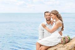 De gelukkige zitting van het jonggehuwdepaar Stock Afbeelding