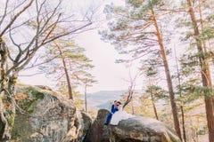 De gelukkige zitting van het jonggehuwdepaar op rotskeien Heuvelslandschap als backround Stock Fotografie