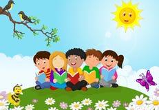 De gelukkige zitting van het kinderenbeeldverhaal op het gras terwijl het lezen van boeken Stock Foto