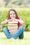 De gelukkige zitting van het studentenmeisje dichtbij stapel van boeken Stock Foto
