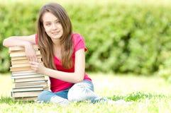 De gelukkige zitting van het studentenmeisje op stapel van boeken Royalty-vrije Stock Afbeelding