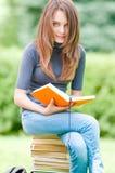De gelukkige zitting van het studentenmeisje op stapel van boeken Stock Foto's