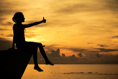 De gelukkige zitting van het tienermeisje op strand Royalty-vrije Stock Fotografie