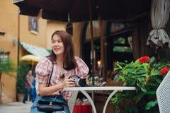 De gelukkige zitting van de vrouwenreiziger in in openlucht koffie in retro uitstekende stad royalty-vrije stock afbeeldingen