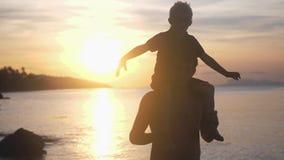 De gelukkige zoon in oogglazen zit op de schouders van zijn vader op tropisch strand bij overweldigende zonsondergang in langzame stock videobeelden
