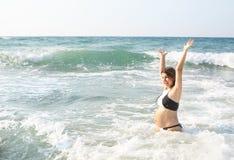 De gelukkige zwangere vrouw heeft pret in het overzees Stock Foto