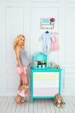 De gelukkige zwangere vrouw houdt een pluchestuk speelgoed Stock Afbeelding