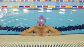 De gelukkige zwangere vrouw zwemt in de pool stock footage