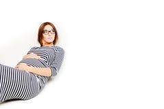 De gelukkige zwangere vrouwen zitten op vloer en aanrakingenbuik Stock Foto