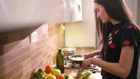 De gelukkige zwart-haired vrouw in huiskleren kookt in de keuken Zij maakt wat verse salade met groene sla stock videobeelden