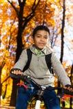 De gelukkige zwarte jongen berijdt een fiets Stock Afbeelding