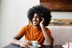 De gelukkige zwarte koffie van de mensenzitting en mobiele telefoon Stock Fotografie