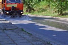 De gemeentelijke nutsauto giet de rijweg op een hete de zomerdag stock foto