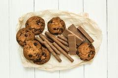 De gemengde chocoladewafel rolt, koekjes en klassieke wafel op een houten witte lijst Zoet-Toothers stock afbeeldingen
