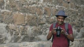 De gemengde mens die van de ras gelukkige toerist foto op zijn dslrcamera nemen die zich dichtbij de beroemde bouw in Europa bevi stock videobeelden