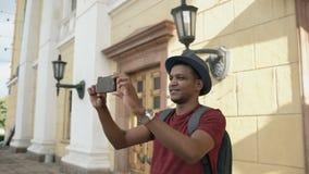 De gemengde mens die van de ras gelukkige toerist foto op zijn smartphonecamera nemen die zich dichtbij de beroemde bouw in Europ stock videobeelden