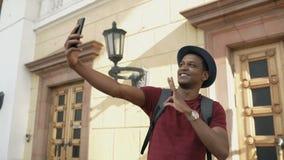 De gemengde mens die van de ras gelukkige toerist selfie foto op zijn smartphonecamera nemen die zich dichtbij de beroemde bouw i stock videobeelden