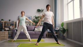 De gemengde ras jonge mens die yoga met Kaukasische vrouw doen concentreerde zich thuis bij de opleiding stock videobeelden