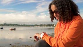 De gemengde tiener die van het ras Afrikaanse Amerikaanse meisje haar slim horloge voor het sociale media of texting met behulp v stock footage