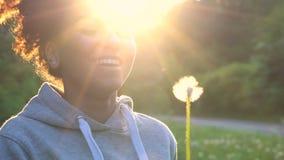 De gemengde tiener van het ras Afrikaanse Amerikaanse meisje of jonge vrouw die, en een paardebloem glimlachen blazen bij zonsond stock videobeelden