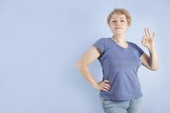De gemiddelde leeftijdsvrouw toont een handgebaar O.k. stock fotografie