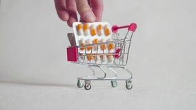 De geneeskunde, de pillen, de drug of de tabletten in een blaar pakken in boodschappenwagentje op witte achtergrond voor gezondhe stock videobeelden