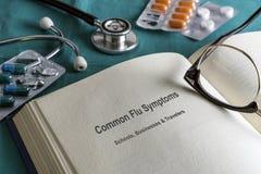 De geneeskunde van de boekpagina van gemeenschappelijke griepsymptomen in scholen, ondernemingen en reizigers, huidig metaforisch royalty-vrije stock foto's