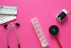 De geneeskundevlakte legt van rode stethoscoop, pillenblaren, container voor drugs en impulsoximeter op roze achtergrond met copy stock fotografie