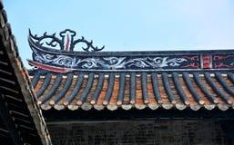 De genomblöta takfottegelplattorna och leraskulpturen av takfot royaltyfria bilder
