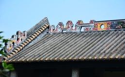 De genomblöta takfottegelplattorna och leraskulpturen av takfot arkivbilder