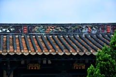 De genomblöta takfottegelplattorna och leraskulpturen av takfot fotografering för bildbyråer