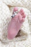 De genomen close-up van babys voet met ringen stock foto