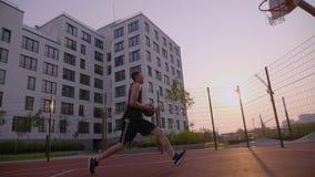 De genoteerde bal van de mensenpraktijk basketbal aan hoepel