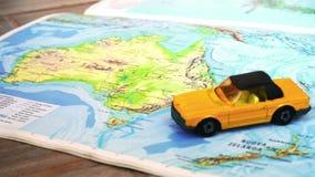 De geografische kaart van Australië met gele convertibele auto stock footage