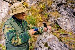 De geoloog onderzoekt een mineralogische steekproef met behulp van een geologische hamer stock afbeelding