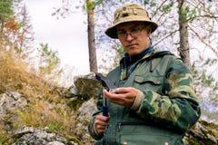 De geoloog onderzoekt een mineralogische steekproef met behulp van een geologische hamer stock foto's