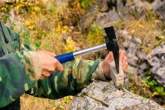 De geoloog onderzoekt een mineralogische steekproef met behulp van een geologische hamer royalty-vrije stock fotografie