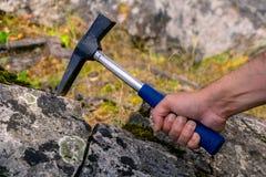 De geoloog onderzoekt een mineralogische steekproef met behulp van een geologische hamer stock afbeeldingen
