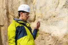 De geoloog onderzoekt een steekproef van steen openlucht royalty-vrije stock fotografie