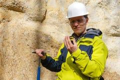 De geoloog onderzoekt een steekproef van steen openlucht royalty-vrije stock foto's
