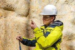 De geoloog onderzoekt een steekproef van steen openlucht stock fotografie