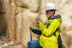 De geoloog onderzoekt een steekproef van steen openlucht royalty-vrije stock foto