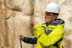 De geoloog onderzoekt een steekproef van steen openlucht royalty-vrije stock afbeeldingen
