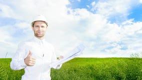 De geoloog in witte helm op groene weide met tekeningen in handen houdt zijn duim tegen Ingenieursbouwer op bouwwerf royalty-vrije stock foto's