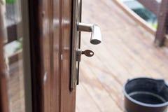 De geopende huisdeur, u kan zien wat buiten is Deurhandvat en sleutel Stock Afbeelding