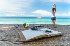 De geopende lege blocnote is op de lijst met zonnebril, telefoon, hoofdtelefoons bij de achtergrond van tropische overzees en het Royalty-vrije Stock Afbeelding