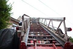 De geopende vrachtwagen van de ladderbrand De brandbestrijders doven dak van het oude huis Royalty-vrije Stock Foto