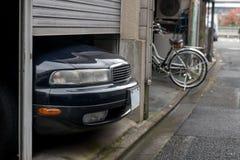 De geparkeerde auto overschrijdt de grootte van een garage Stock Afbeeldingen